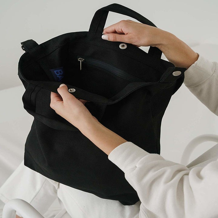 Model opening black canvas tote