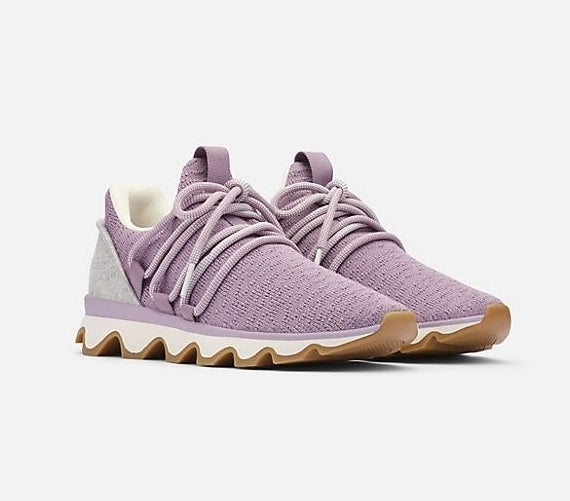 The shoes with oversized scalloped sole,s grey on the heels, and lilac knit body with lilac laces