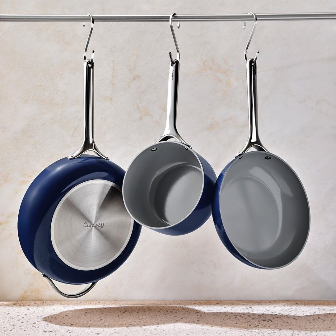 a set of dark blue colored pans hanging from a pole