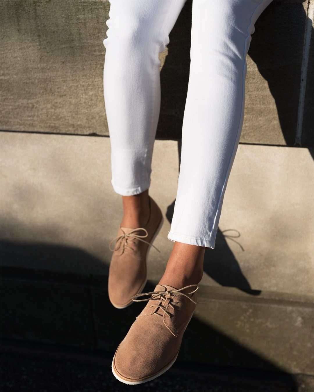 Model wearing the sneaker-style shoe with brown suede body, white sole, and laces