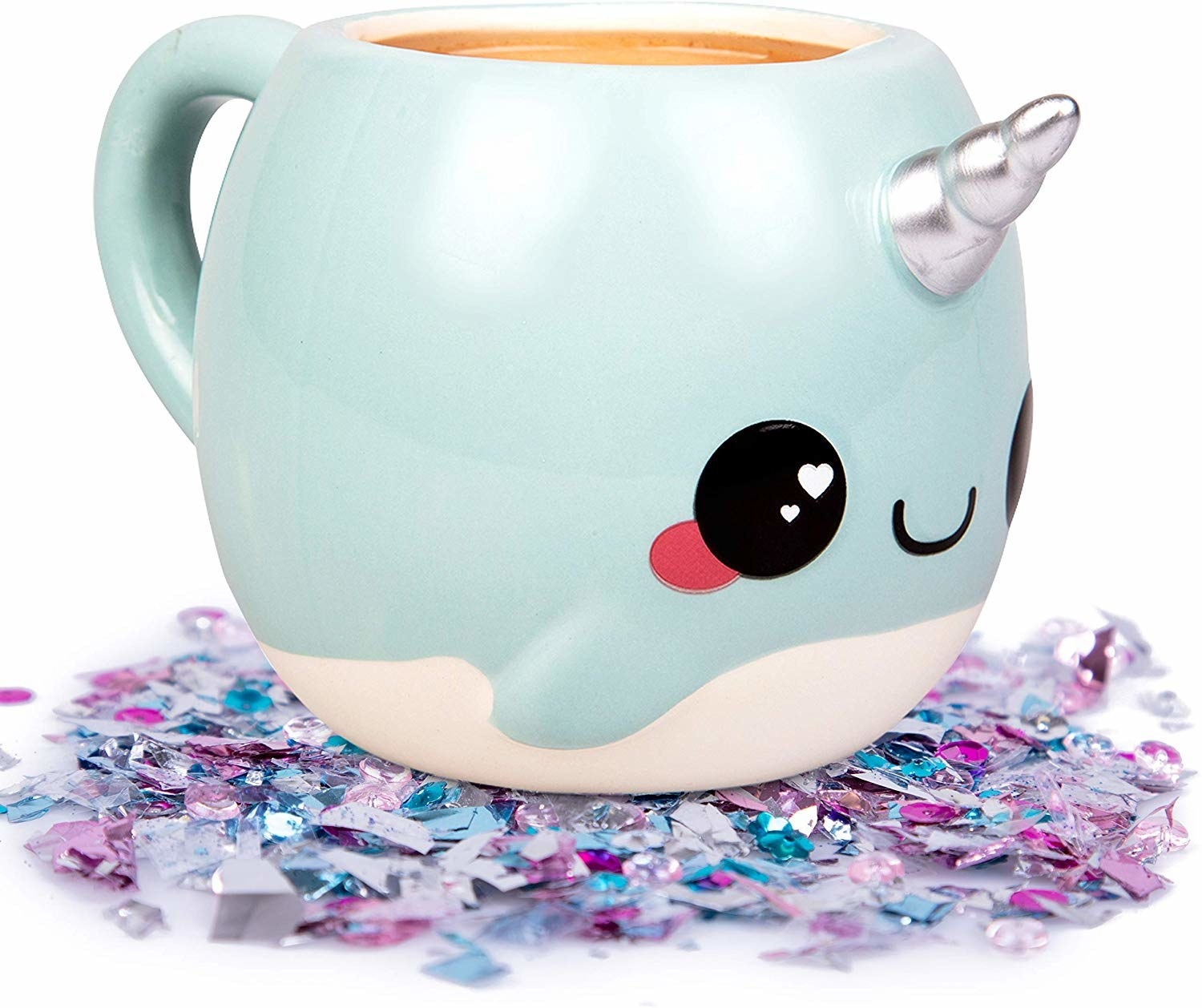coffee mug shaped like light blue cartoon narwhal with a silver unicorn horn and hearts in its eyes