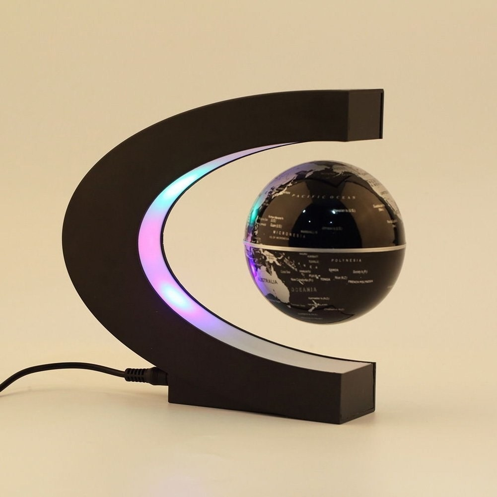 A black levitating globe device with a wire plugged in