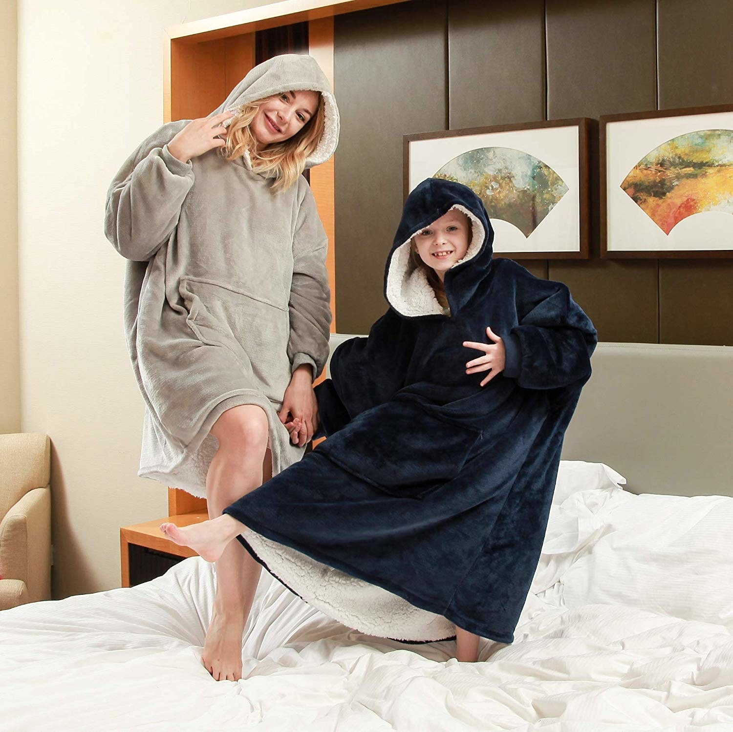 An adult and a child standing on bed wearing a soft oversized hoodie