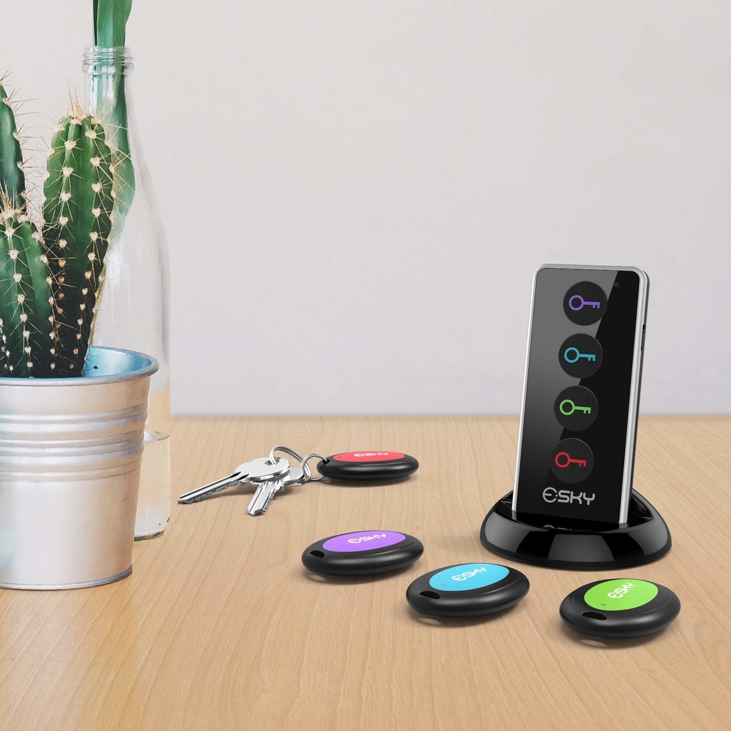 the black small remote-shaped device with buttons with different colored keys on it and small round devices with matching colors sitting below it