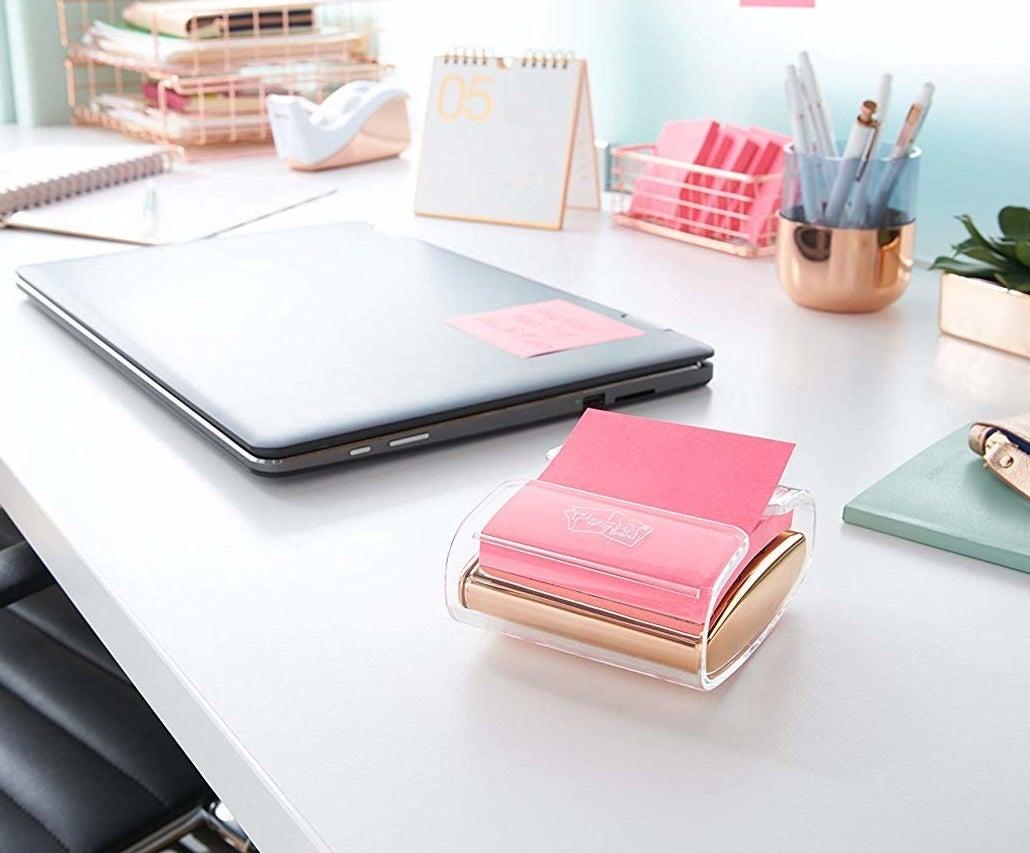 A sticky note pad dispenser next to a closed laptop on a desk