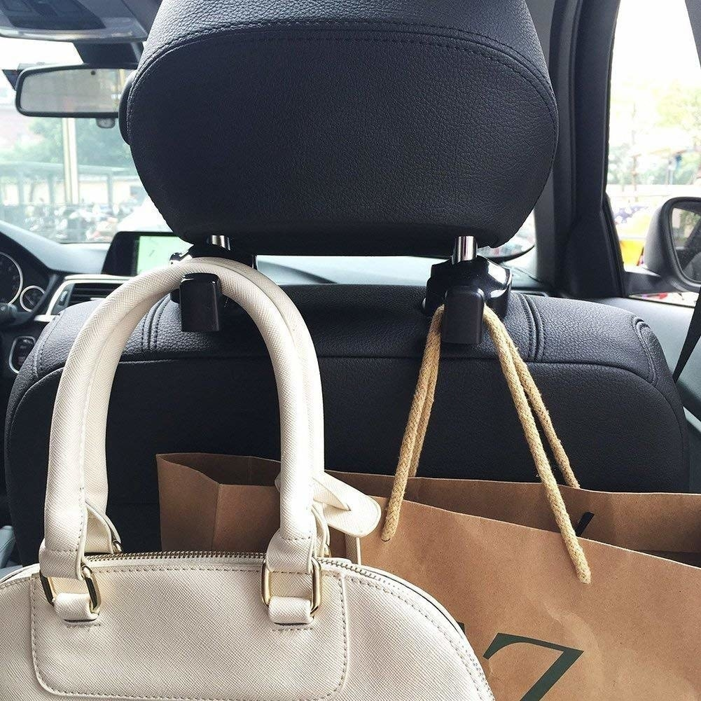 A shopping bag and a hand bag hanging on the back of a car headrest