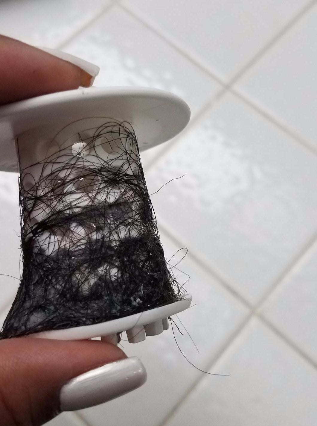 Same reviewer holding the TubShroom covered in hair
