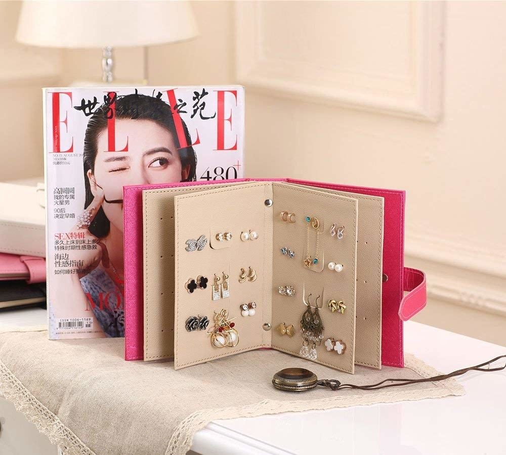 An open earring storage book holding several pairs of earrings next to a magazine
