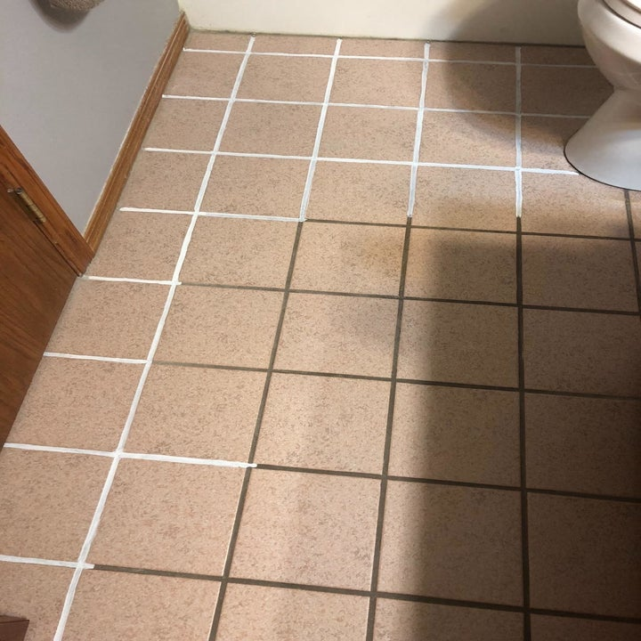 A tiled bathroom floor with white grout from the pen and brown grout on parts not yet marked