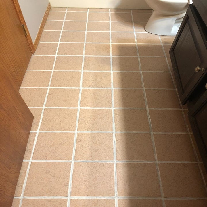The same bathroom floor with completely white grout between the tiles
