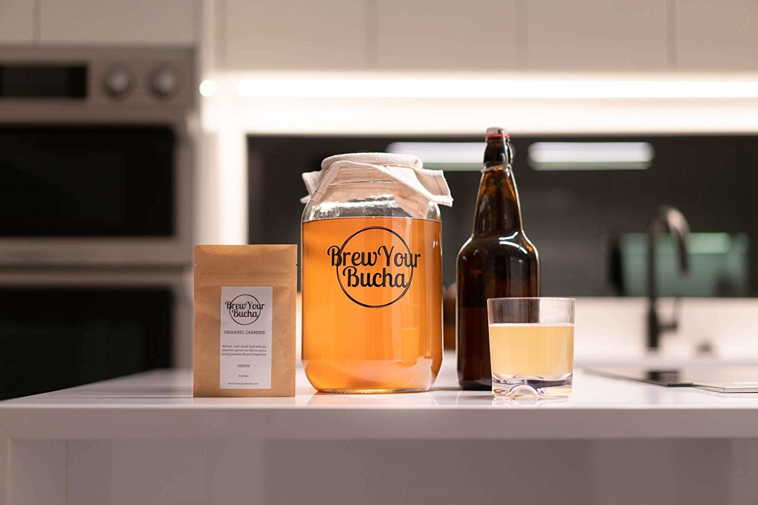 A large glass jar that says brew your bucha on it There a paper bag, a large glass bottle and a small glass of kombucha beside it