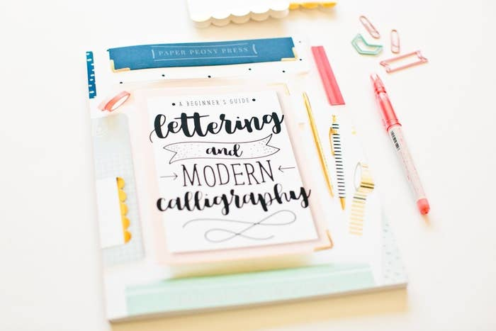 A small craft book called A Beginner's Guide to Lettering and Modern Calligraphy on a desk with a pen and paper clips beside it