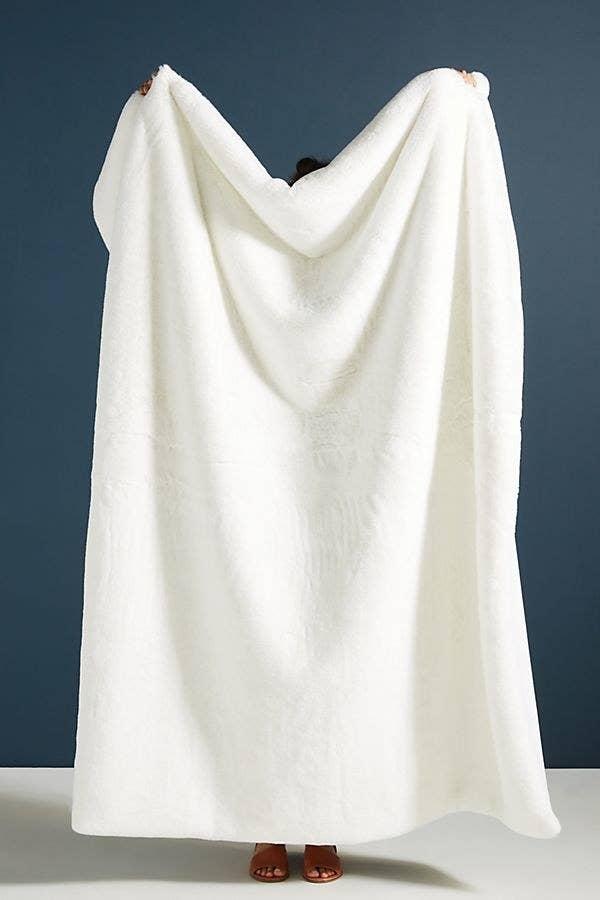 model holds up fluffy blanket