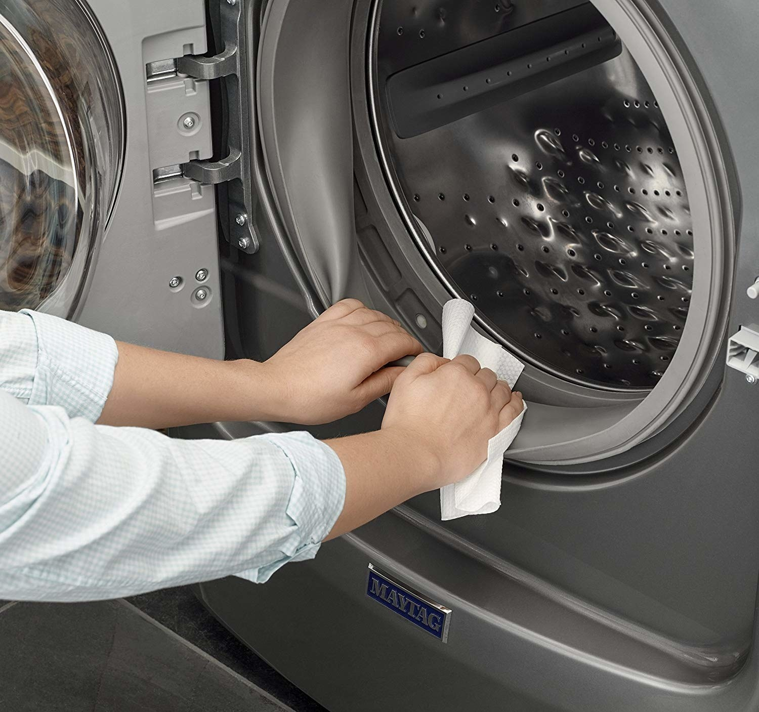 A person cleaning the inside of their washing machine with a thick cloth