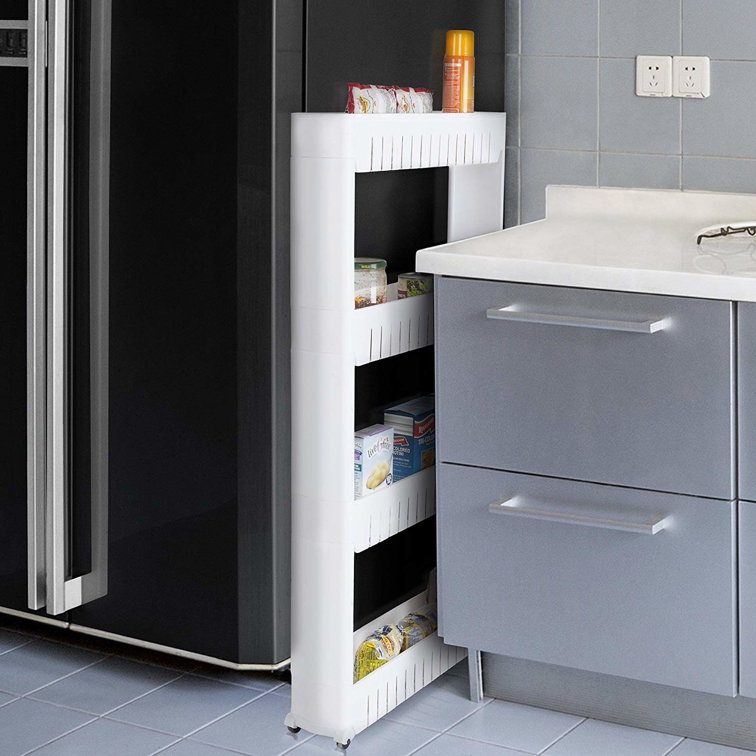 A tall, thing storage unit with four tiers placed between a refrigerator door and a counter top