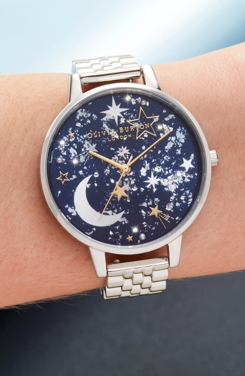 a silver bracelet watch with a navy blue face filled with gems and stars