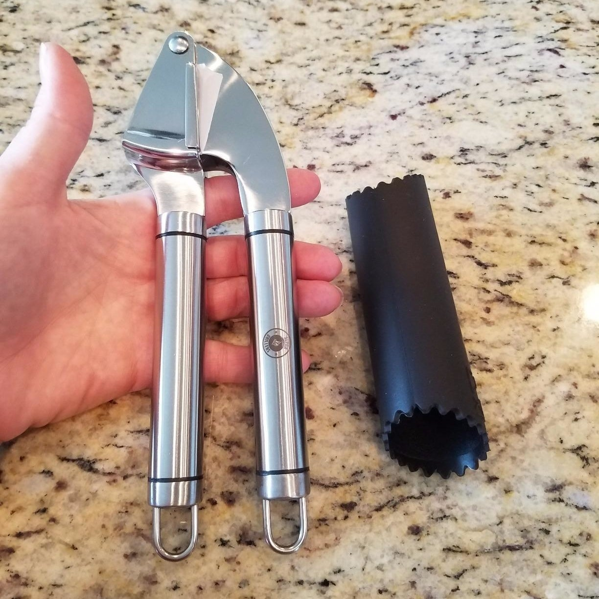 A reviewer holding the garlic press