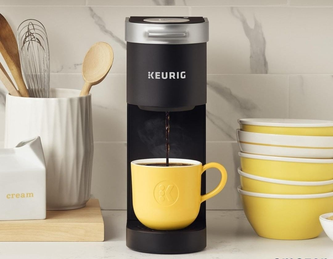 A Keurig machine dripping coffee into a cup