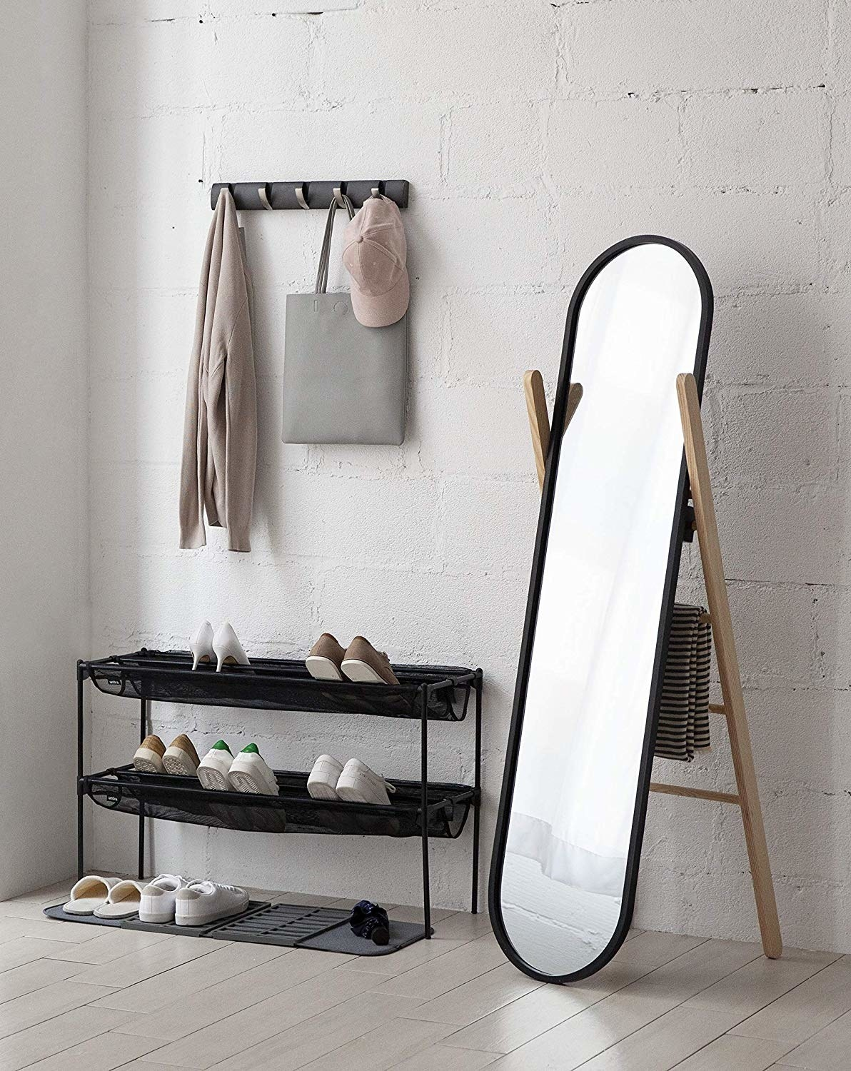 The floor length mirror near an entryway propped next to a shoe rack and wall hook