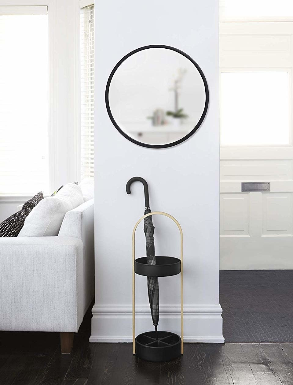 The round mirror is hung on a narrow wall above an umbrella stand