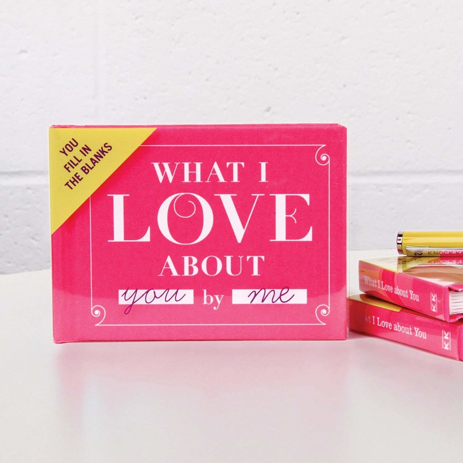 """a small pink book that says """"what I love about you by me"""" on it"""