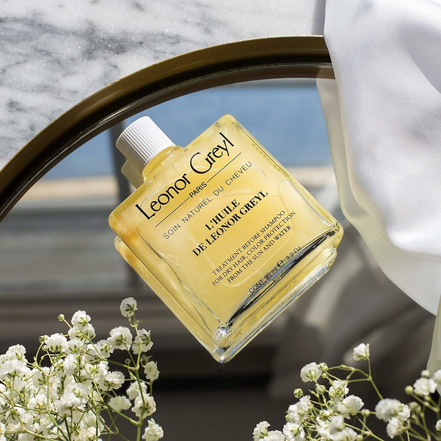 A bottle of Huile de Palme Beautifying Oil laying on a tray