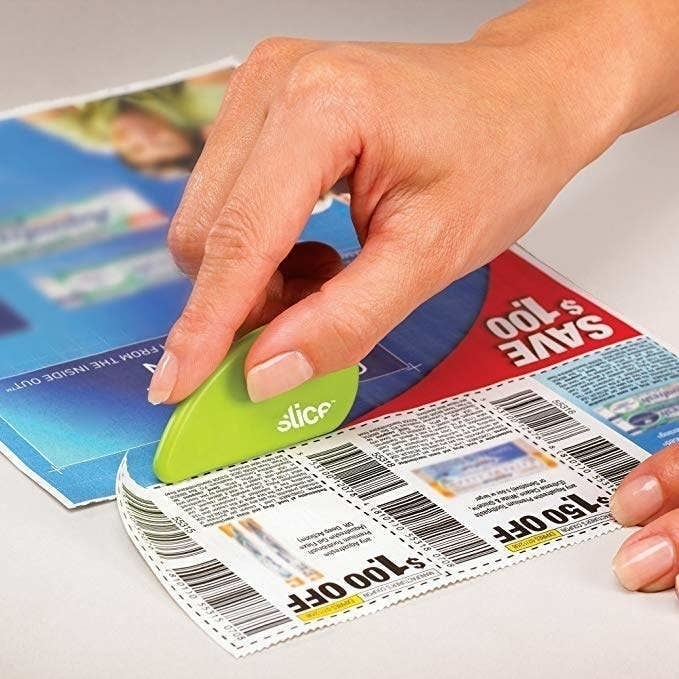 a person using the cutter to cut out coupons