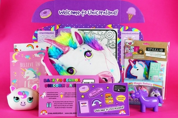An unpacked dream box featuring unicorn plushies and toys, coloring books, themed back-to-school guide, and other items