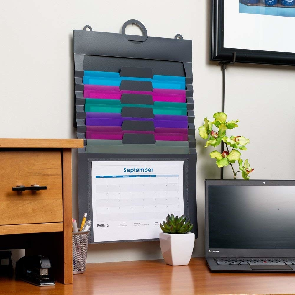 plastic organizer hanging flat against a wall with six different removeable interior file folders