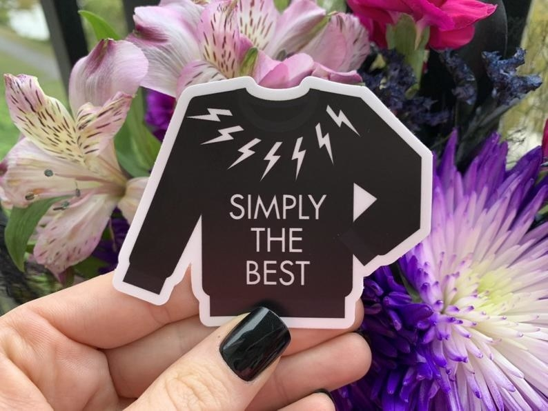 "A hand holding a sticker shaped like David's lightning bolt sweater with the text ""Simply The Best"""