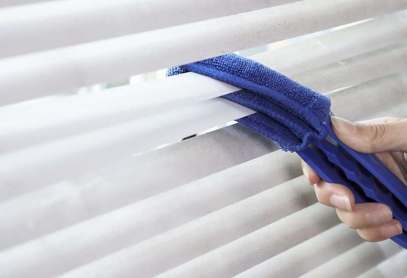 a person using the microfiber tool to clean blinds