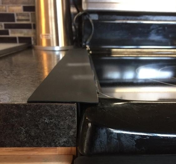 Reviewer's picture of the gap cover placed between their stove and counter