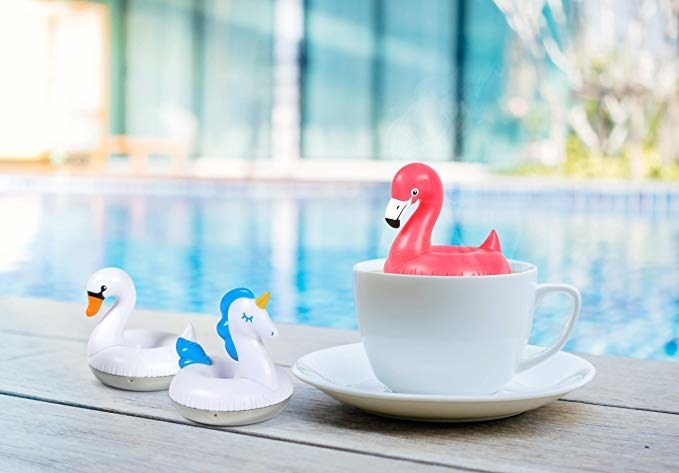 The flamingo floatie tea infuser sitting in a cup next to swan and unicorn floaties