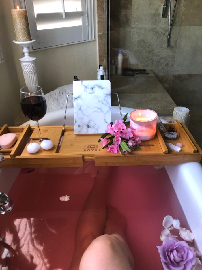 A bamboo tray sitting on top of a bathtub filled with pink water and flowers.