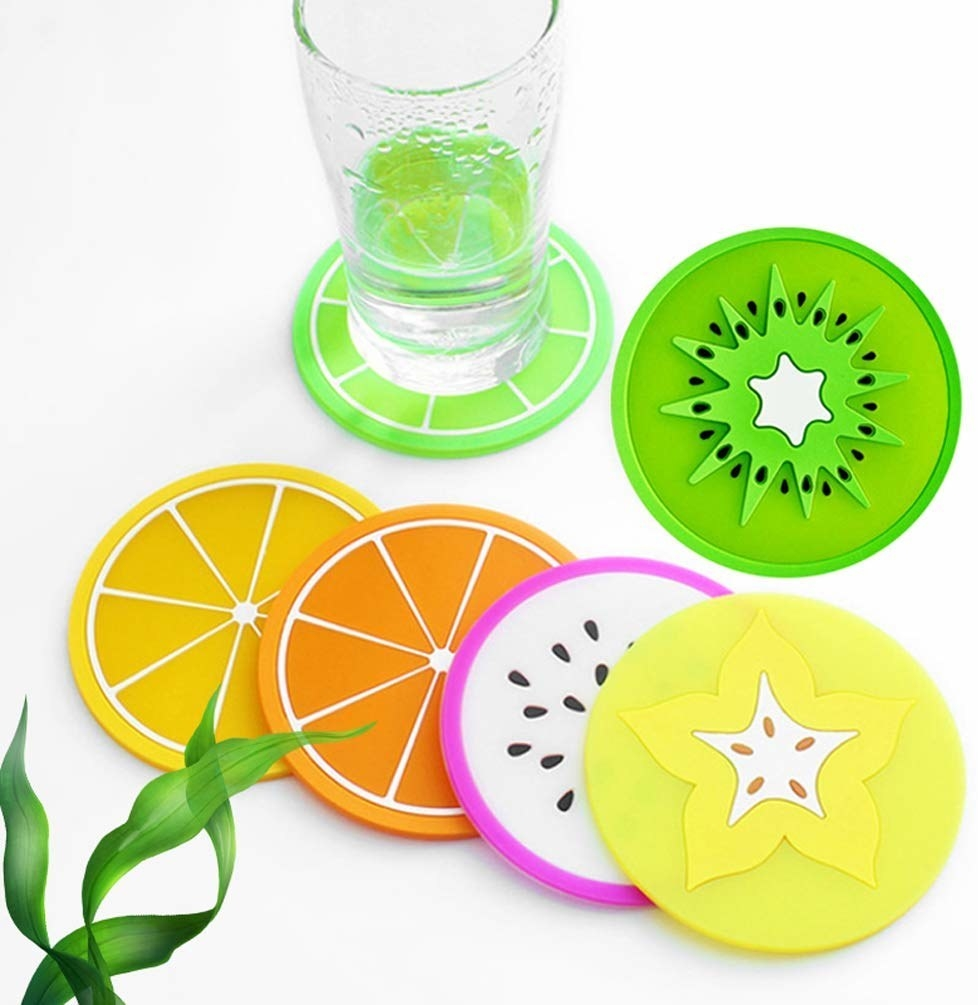 A glass sitting on one of the fruit coasters, surrounded by others