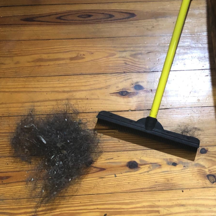 A photo of the same yellow and black squeegee broom on a hardwood floor with a big clump of hair that's presumably been corralled by the broom.