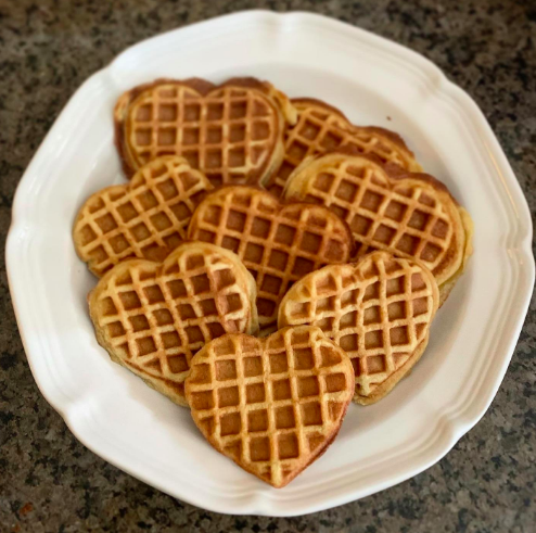 A white plate holding heart-shaped waffles that are the width of a fist.