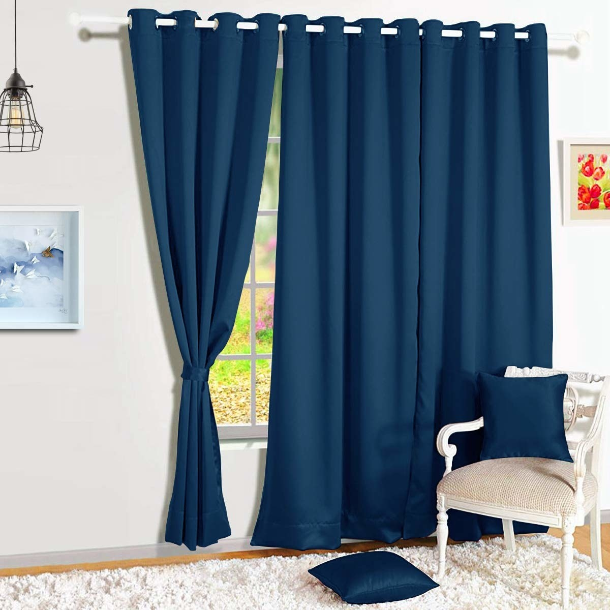 Blue full length blackout curtains in front of a window in a bedroom
