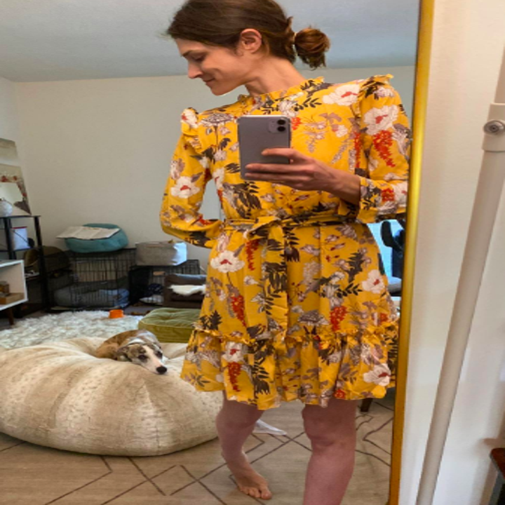 Reviewer wearing the above-the-knee dress in yellow floral