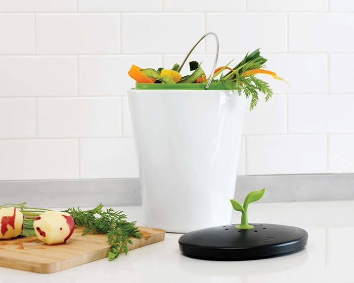 small white bin with handle, food scraps inside and a black lid next to it