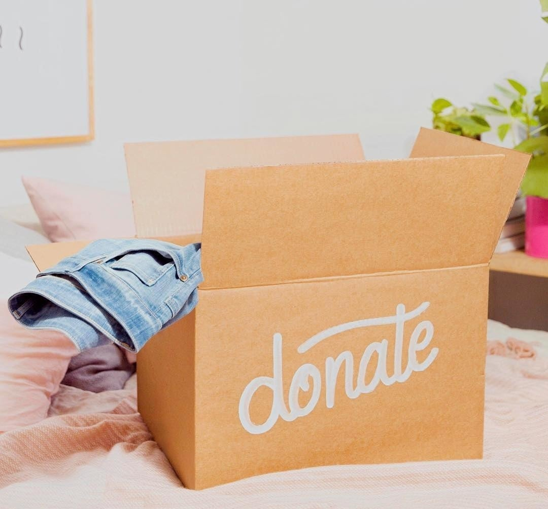 "A box with the word ""donate"" written on it, a pair of jeans sticking out of the top"