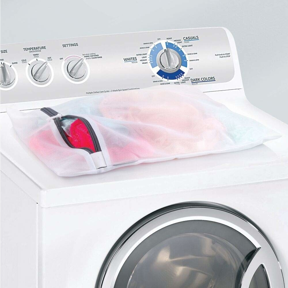 laundry bag filled with clothes resting on top of washing machine
