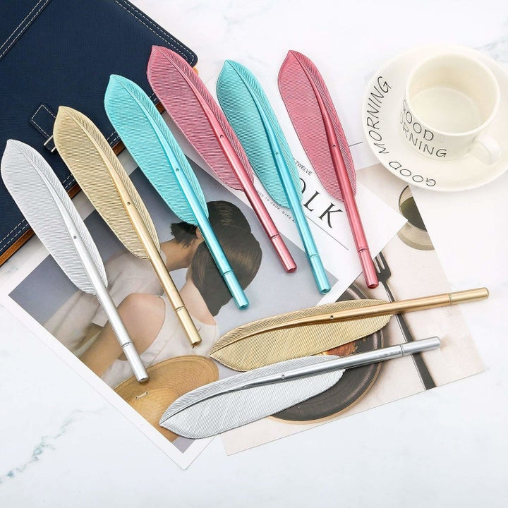The metallic feather-shaped pens in pink, teal, gold, and silver