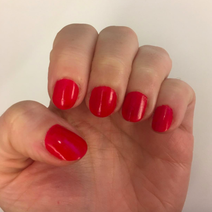 Reviewer photo showing their red fingernails with the varnish on them but not noticeable