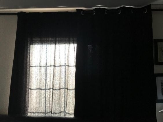 Window with regular black curtains on one side with light shining through. The blackout curtain is on the other side and has no light shining through at all.