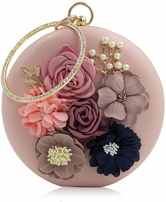 A pink clutch with different coloured flower embellishments on it