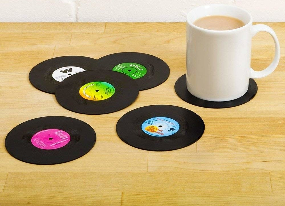 A set of six plastic coasters that look like vinyls One coaster has a coffee mug resting on it