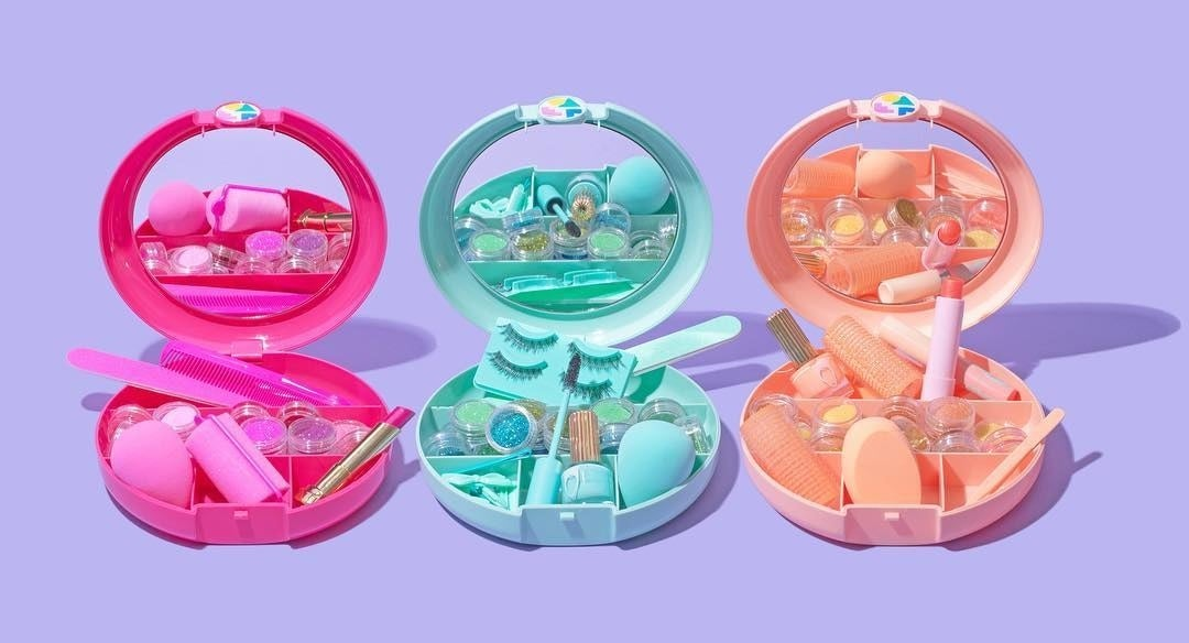 Three small round plastic makeup cases next to each other Each has a mirror on the inside and is filled with beauty products and tools