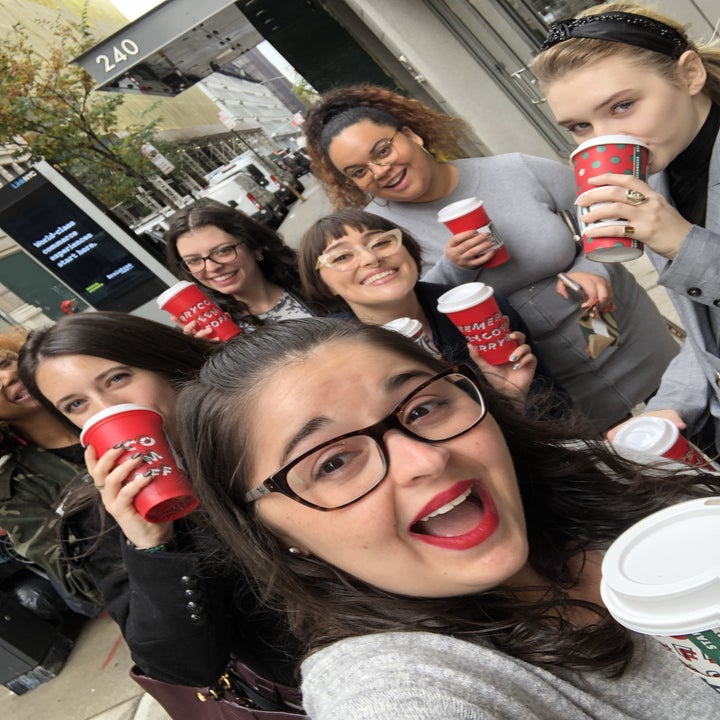 a buzzfeed editor wearing the red lipstick while posing with a group of people with starbucks cups