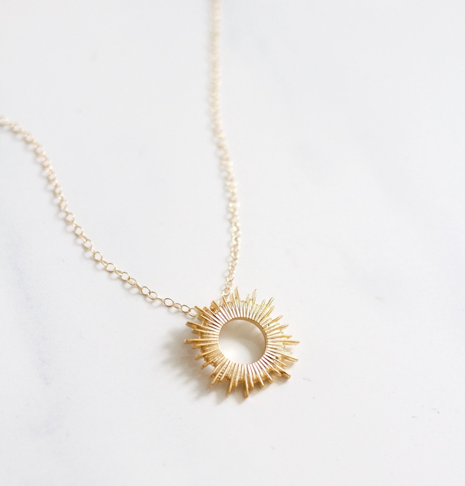 the gold sunburst necklace on a chain